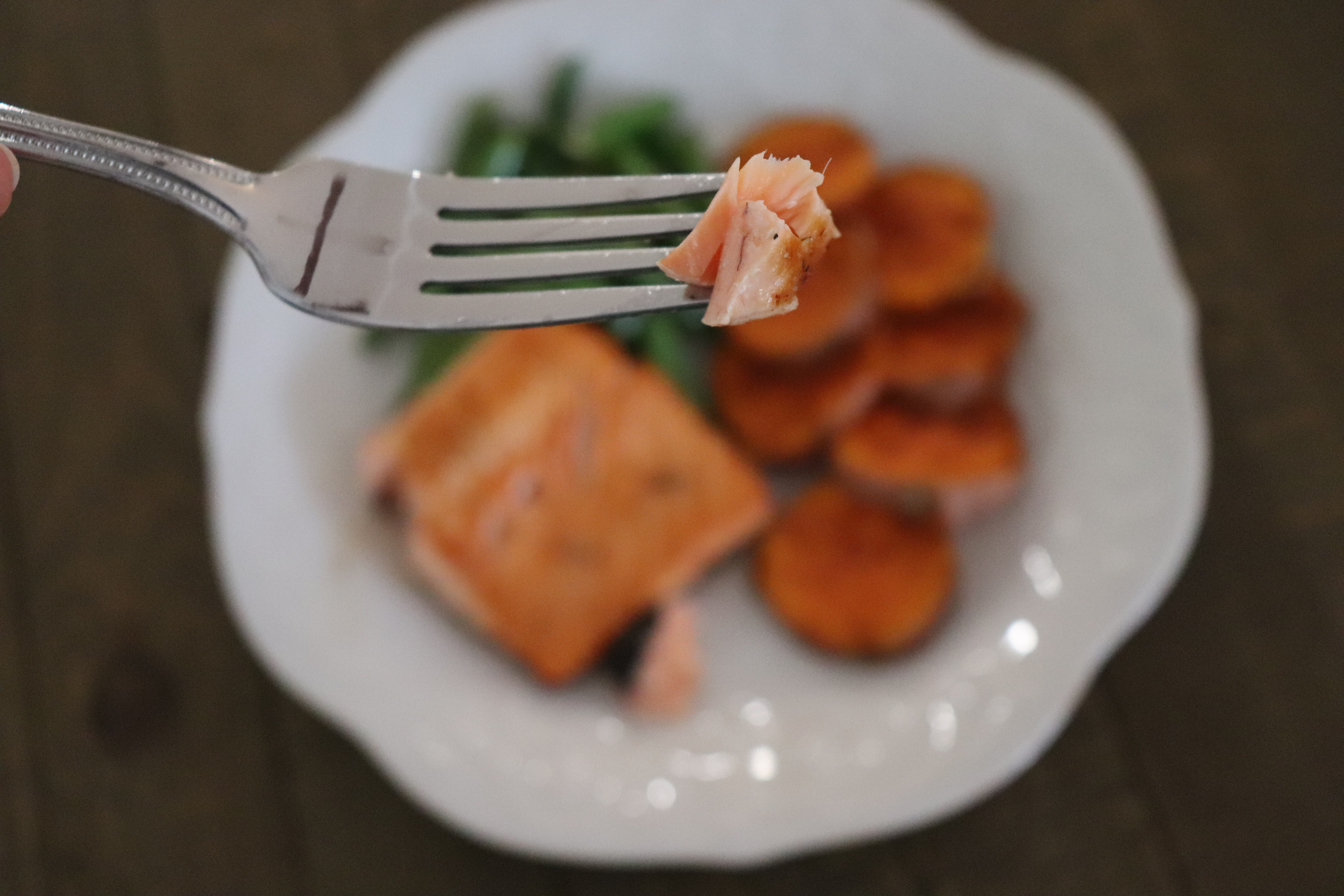 Bite of flaky salmon with a plate of salmon, sweet potatoes and green beans in the background