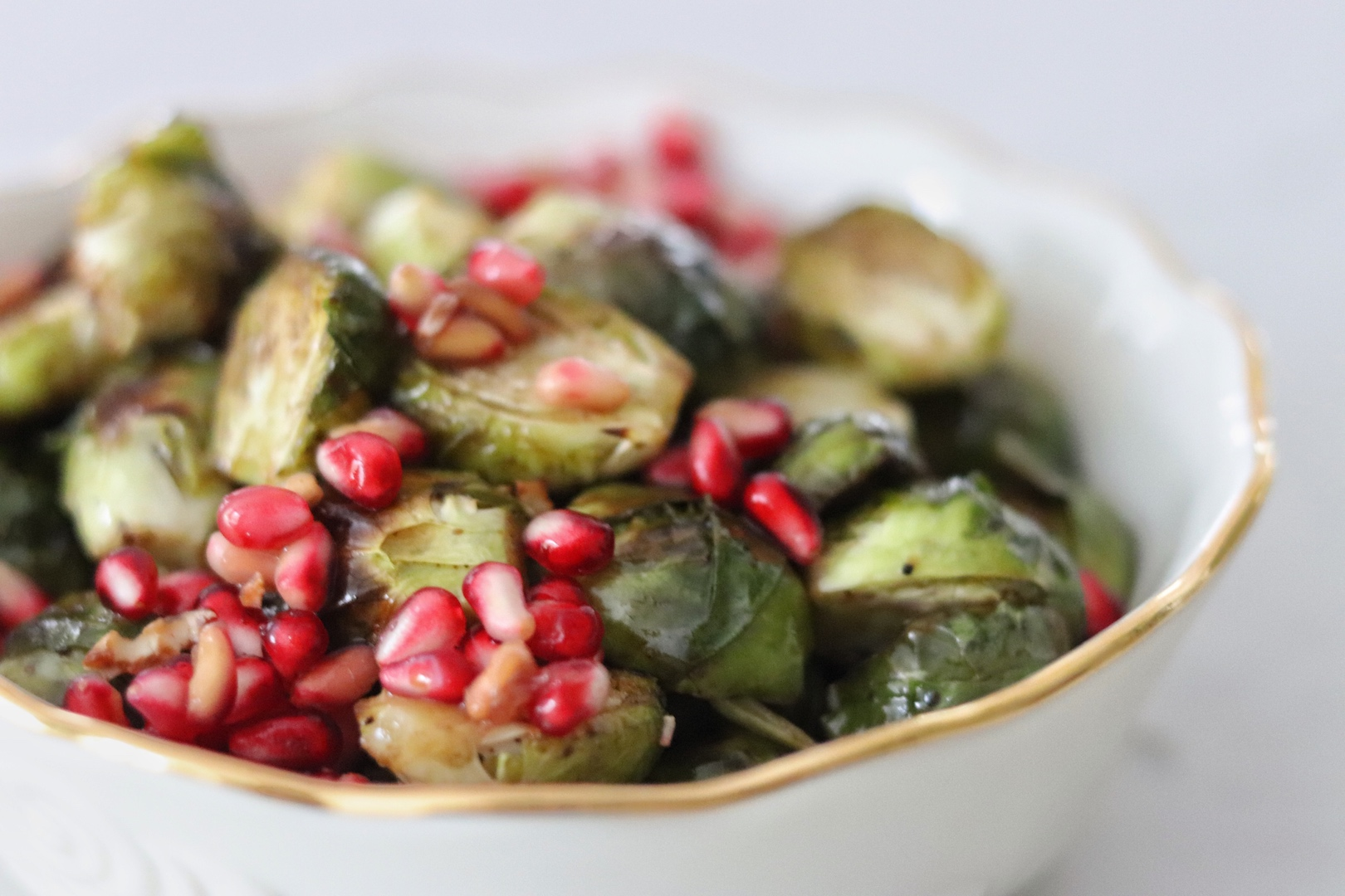 Roasted Brussels Sprouts with Balsamic and Pomegranate Seeds in a white bowl with a gold rim