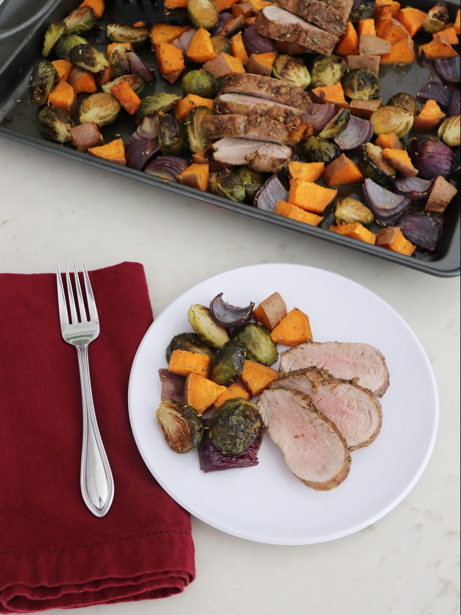 Plate of Sheet Pan Honey-Balsamic Pork Tenderloin with Sweet Potatoes and Brussels Sprouts with pan in the background