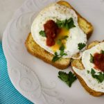 Savory French toast topped with fried eggs, salsa, and chopped parsley