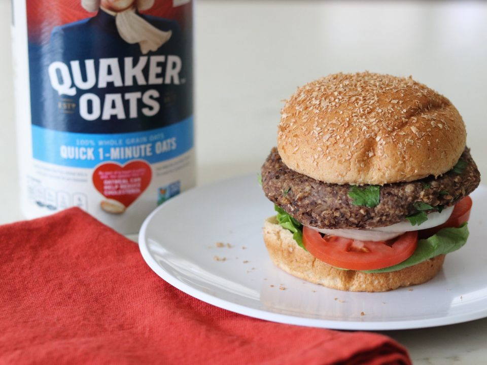 Oat Black Bean Vegetable Burger on a bun with a carton of Quaker Oats in the background