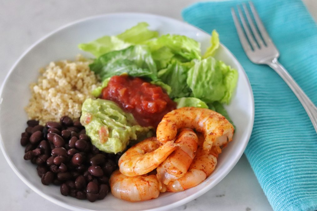 Baja Shrimp Bowl with romaine lettuce, quinoa, black beans, shrimp, salsa, and guacamole