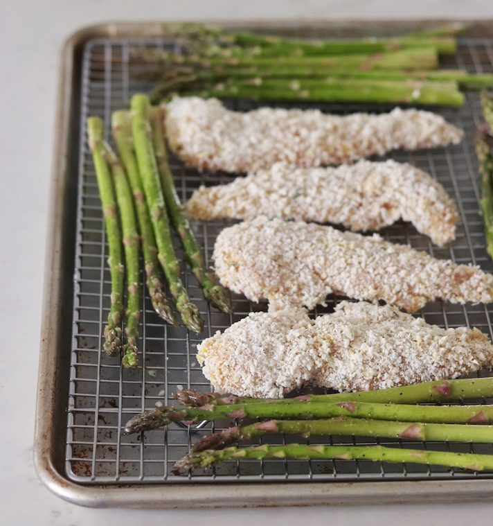 A sheet pan with crispy coated chicken and asparagus