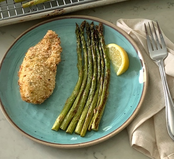 Plate with a serving of Crispy parmesan chicken and asparagus