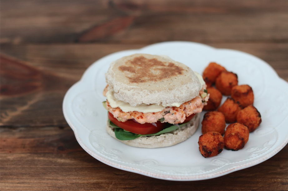 A salmon burger on an English muffin with Lemon-Dijon Aioli, spinach, tomato, and onion on a plate with sweet potato tots