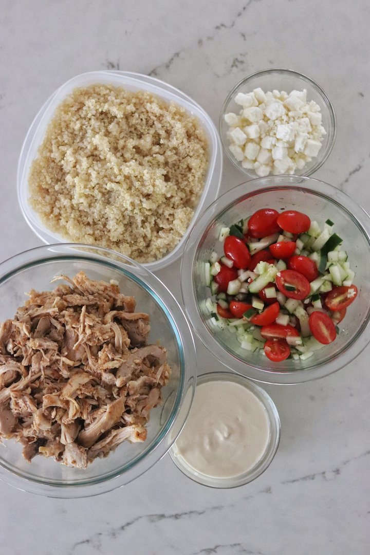 Bowl of Instant Pot Greek Chicken, Tomato and Cucumber Salad, cooked quinoa, and Tahini-Lemon Sauce