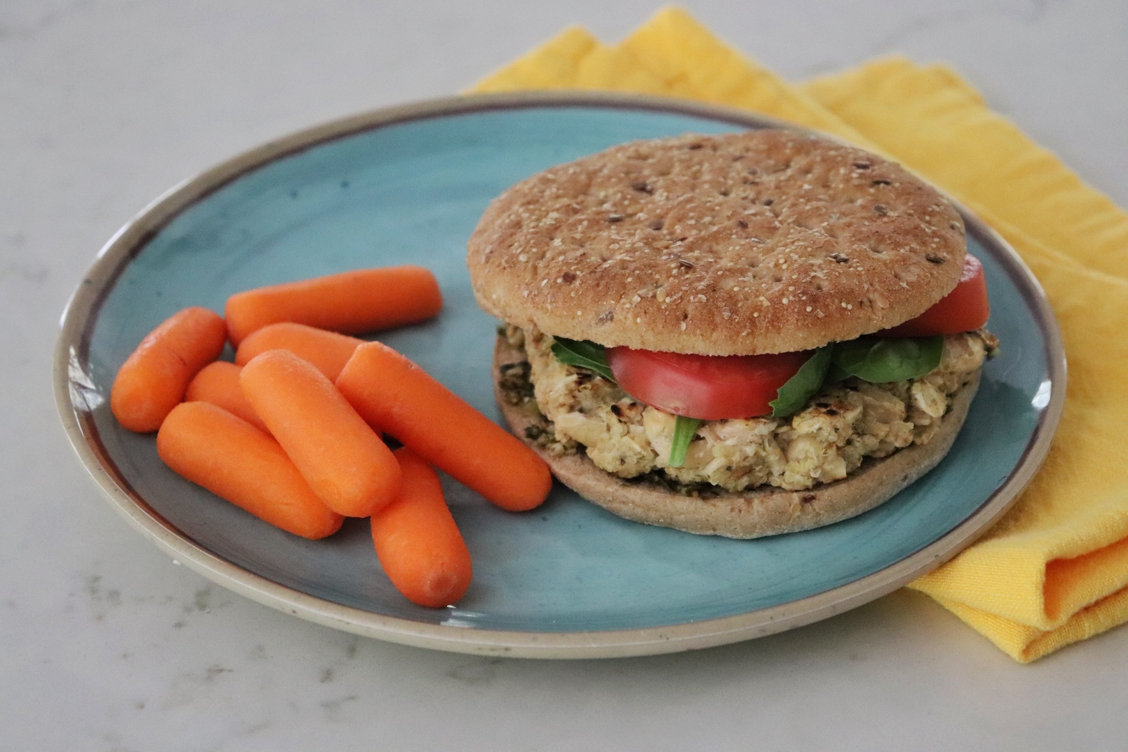 Flaxseed Quinoa and White Bean Burger on a blue plate with carrots
