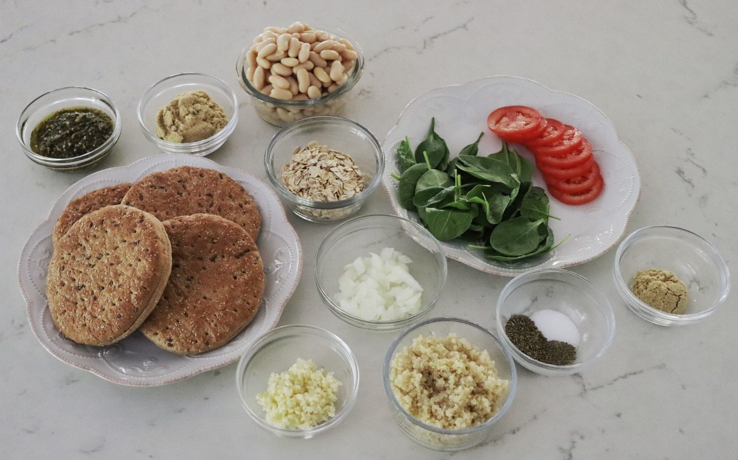All ingredients for Flaxseed Quinoa and White Bean Burgers in small clear glass bowls