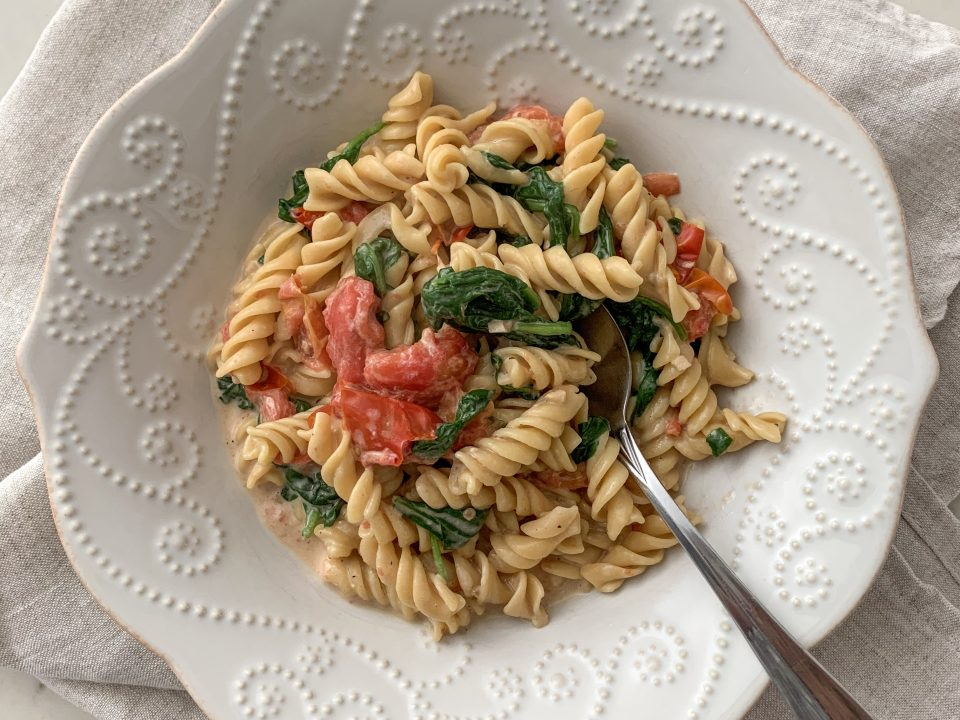 A while bowl filled with a serving of Creamy Tomato Chickpea Pasta with Spinach